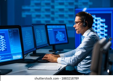 Call-center worker is speaking with the client by headset. Workplace of the professional support operator in office.