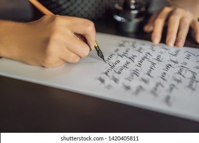 Calligrapher hands writes phrase on white paper. Bible phrase about love Inscribing ornamental decorated letters. Calligraphy, graphic design, lettering, handwriting, creation concept