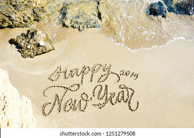 Calligraphy, handwriting, Happy new Year 2019 on sand on the beach.