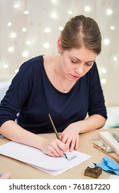 calligraphy, painting, creativity concept. adorable woman artist with fair haires and delicate arms wearing dark blue shirt and golden ring, she is drawing sticks with thin quill