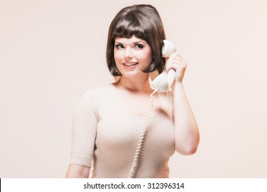 Calling Brunette Woman in Pink Retro 1960s Fashion.