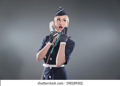Calling retro blonde stewardess wearing blue suit. Holding white vintage phone. Studio shot against grey.