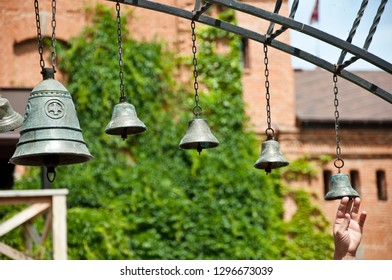 Calling worshippers to the church. Bells ringing on wind. Church bells hanging outdoor. Metal bells on metallic chains hung on arc in church yard. Calling to christian mass or service of worship.