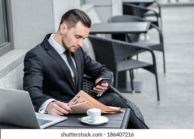 Calls customers. Businessman holding a phone and is going to call customers