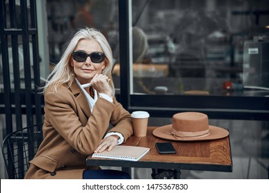 Calm adult lady sitting at the cafe table outside with notebook and coffee