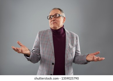 Calm adult person standing isolated against the grey background and thoughtfully looking into the distance with his hands up at the helpless gesture
