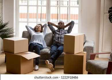 Calm African American couple in love relaxing leaning back on couch, sitting together, tired resting man and woman just arrived, unpacked cardboard boxes with belongings, moving concept, new house