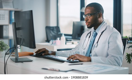 Calm African American Family Medical Doctor in Glasses is Working on a Desktop Computer in a Health Clinic. Physician in White Lab Coat is Browsing Medical History Behind a Desk in Hospital Office.