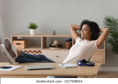 Calm african positive woman put hands behind head legs on desk relaxing at home freelancer finished work feels satisfied dreaming about successful future, no stress reduce anxiety and fatigue concept