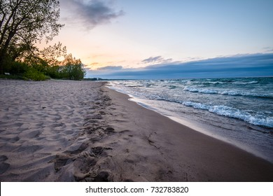 A calm afternoon at a beach in Wisconsin on Lake Michigan; sun setting in the background, as the sky begins to turn a faint orange color over the water.