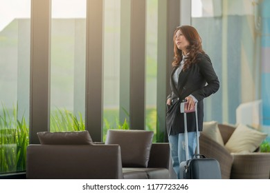 Calm asian businesswoman is standing and looking through the window in airport lounge. Copy space
