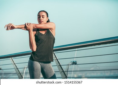 Calm athlete standing next to the banister and warming her muscles up