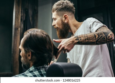 Calm attentive barber with long beard and tattoos on his arms touching long hair of his client and looking into the mirror