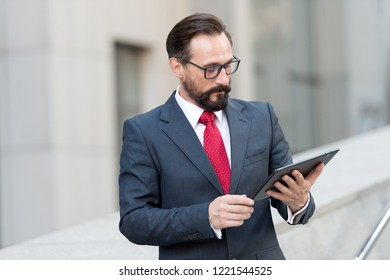 Calm attentive man in elegant suit getting ready for the working day and thoughtfully reading the information in his tablet