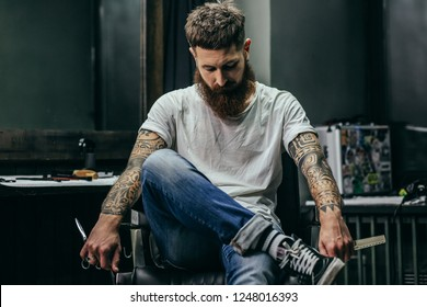Calm attractive bearded barber holding scissors and comb while sitting in the armchair of his popular barber shop