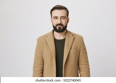 Calm attractive bearded person in coat over green pullover with normal expression, standing against gray background. Man stands in queue to buy newspaper and coffee near office building