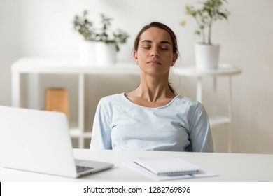 Calm attractive woman relaxing at workplace, sitting with closed eyes, leaning back in chair, meditating at work, deep breath, no stress concept, businesswoman, student resting after finish work