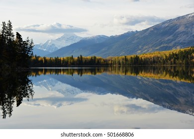 Calm autumn view of reflection of Mt Edith Cavell in Pyramid lake in front of cloudy sky in Jasper National Park, Alberta, Canada