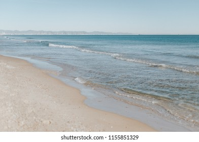 Calm beach with soft waves. El Saler, Valencia, Spain.