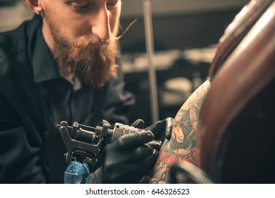 Calm bearded man creating tattoo on hand of woman. She sitting on chair