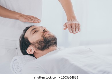 calm bearded man lying on massage table and hands of healer doing reiki treatment session