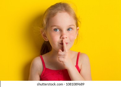 Calm beautiful blonde girl looking camera and making silence gesture isolated over yellow