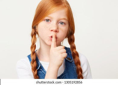 Calm beautiful girl with braided red hair in two long plaits looking camera and making silence gesture isolated over white background
