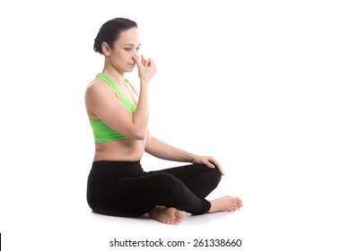 Calm beautiful girl practicing hatha yoga nadi shodhana pranayama (Alternate Nostril Breathing), sitting cross-legged in Easy Pose, Sukhasana, meditation, Vishnu mudra, copy space