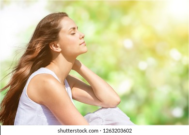 Calm beautiful smiling young woman with ponytail enjoying fresh air outdoor, relaxing with eyes closed, feeling alive, breathing, dreaming. Copy space, green park nature background. Side view portrait