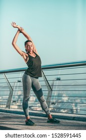 Calm beautiful sportswoman standing by the banister with closed eyes and stretching arms up