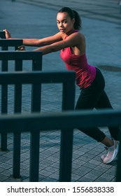 Calm beautiful woman in sporty clothes training outdoors with hands on the banister and looking away