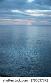 Calm blue evening sea water with clouds