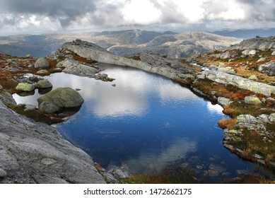 Calm blue lake with reflection of clouds and sky in rocky Norwegian highlands. Kjerag mountain. Western Norway.