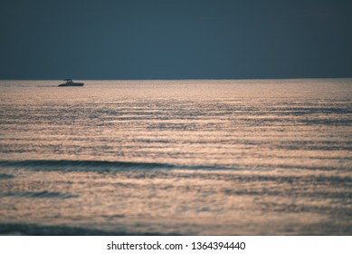 calm blue sunset over clear water in baltic sea. minimalistic image with straight horizon line and texture in water from waves - vintage retro film look