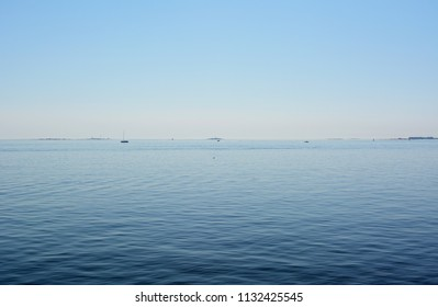Calm blue waters and clear sky above in the Gulf of Finland. Small boats and islands are dotted in the distance.