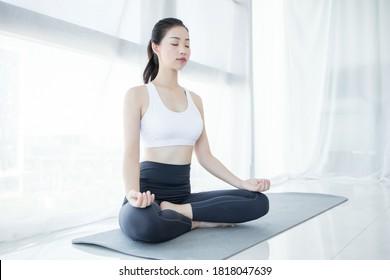 Calm brunette Geschäftsfrau, die Yoga im Büro praktiziert