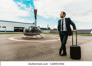 Calm businessman in dark suit thoughtfully looking into the distance while standing on the helicopter platform with one hand on the rolling bag