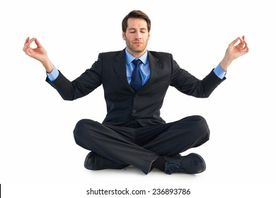 Calm businessman sitting in lotus pose on white background