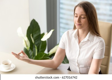 Calm businesswoman meditating in office chair. Female office worker relaxing on workplace. Business lady yoga exercise. Girl resting and relieves work stress with spiritual practices or autosuggestion