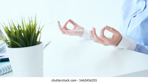 Calm businesswoman meditating at work, focus on female hands in mudra, close up view. Peaceful mindful employee practicing exercises at workplace. Office stress problem concept.
