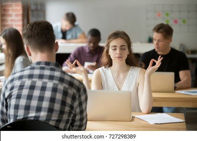 Calm businesswoman meditating in yoga pose in modern office setting. Business lady taking care of her health during break. Reducing discomfort at workplace, staying in focus, stress relief at work.
