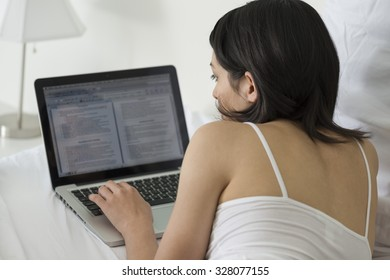 Calm Caucasian young woman with medium black hair in athletic costume using laptop