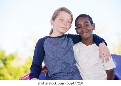 Calm cheerful boy with cute adopted brother embracing outside