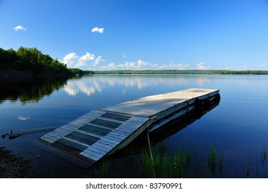 Calm Clear Northern Maine Lake waters with reflected puffy white clouds and wooden dock