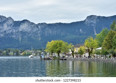 Calm cloudy day on lakefront of Attersee with mountains in background in late summer.