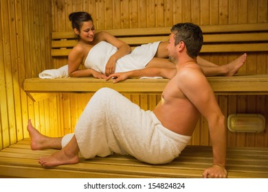 Calm couple relaxing in a sauna and chatting wearing white towels