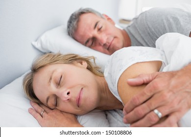 Calm couple sleeping and spooning in bed in bedroom at home