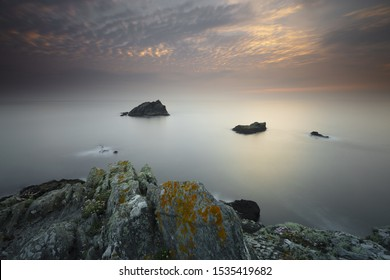 A calm day at the ocean with rocks in the middle and the sky shining lightly in Pentire Point East, Cornwall, UK