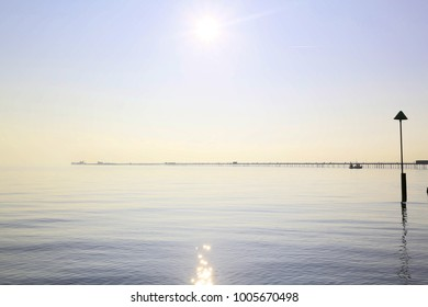calm day with sun low in the sky, showing southend mile long pier and the horizon line