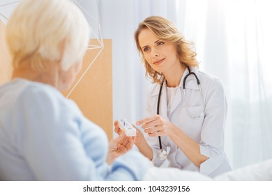Calm doctor. Experienced clever reliable doctor sitting in front of her ill senior patient and looking friendly while pointing to a convenient tiny pillbox